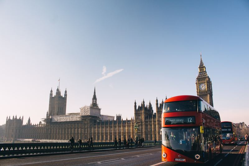 ms in uk : british double decker red bus on bridge over thames river with big ben and palace of westminister in the background