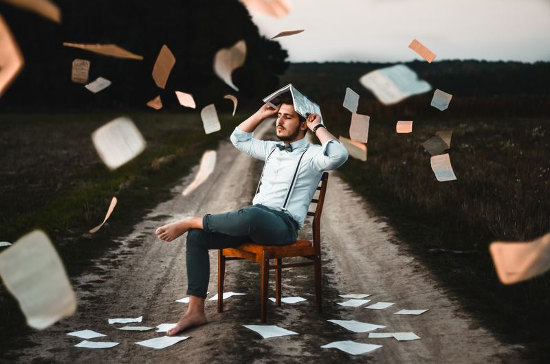 write SOP : person sitting on wooden chair in middle of dirt road with papers falling from sky